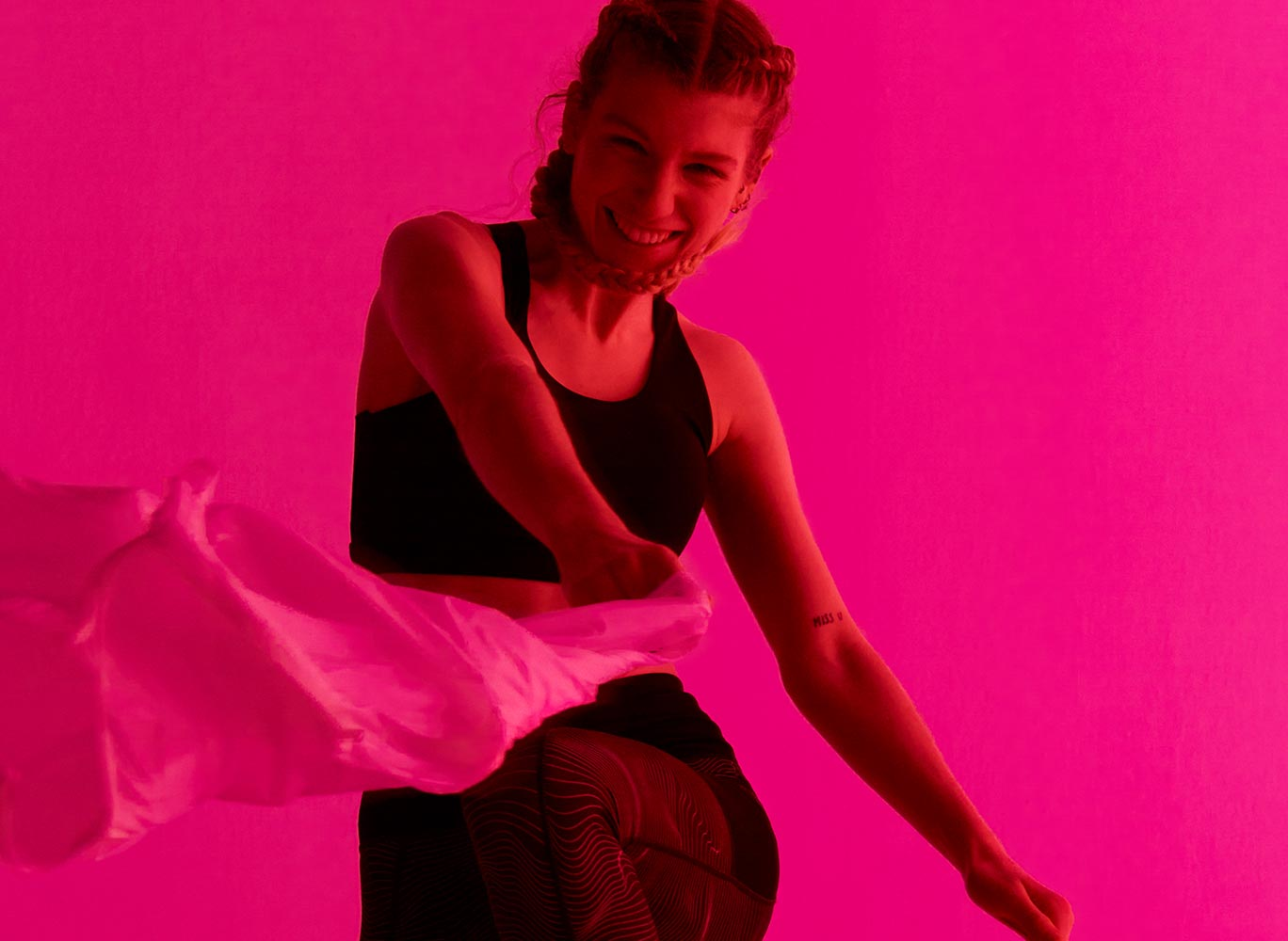 Person in Superdry clothing looking directly at camera lens with pink background